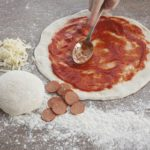 Fresh pizza base with sauce